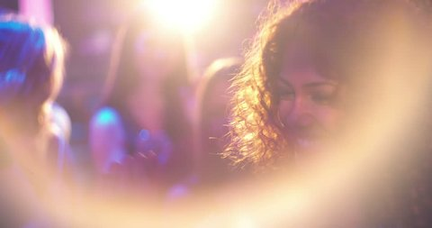 Young beautiful woman with middle eastern decent and curly hair dancing for cheerful and being festive at party in nightclub with disco lights, friends and lens flare