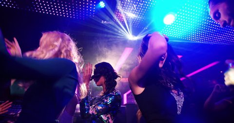 Young attractive blond woman joyful and dancing at a nightclub with disco lights celebrating a party with friends