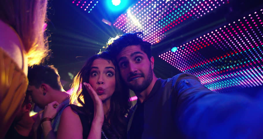 Fashionable friends at nightclub party taking selfies and pulling faces for the photo with people, music and disco lights in the background