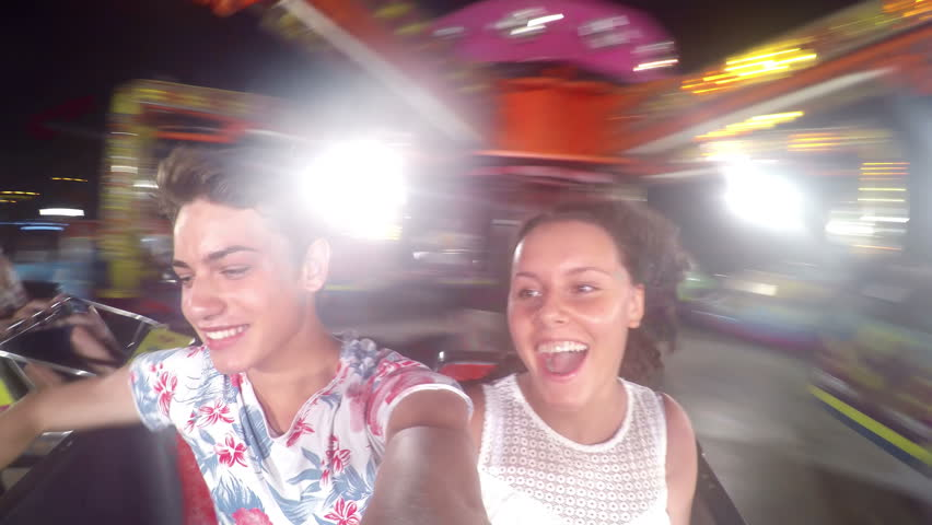 Ride in motion in theme park during the evening, young couple fun