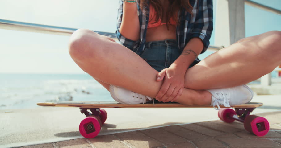 Teen hipster girl looking at the sea while sitting on her skateboard on a paved walkway at the beachfront and holding her phone