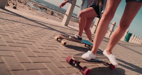 Unrecognizable low angle shot of teen girls wearing shorts and riding their skateboards along a paved walkway at the beachfront in summer