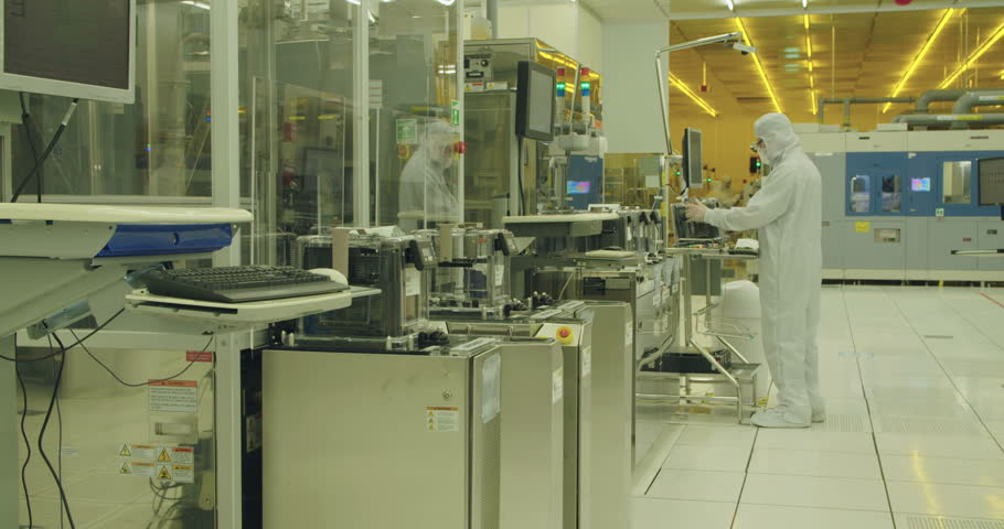 Workers in clean suits in a semiconductors manufacturing facility