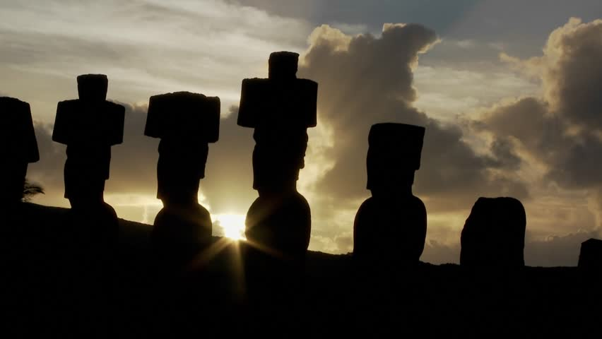 The sun peeks out from behind an Easter Island statue.