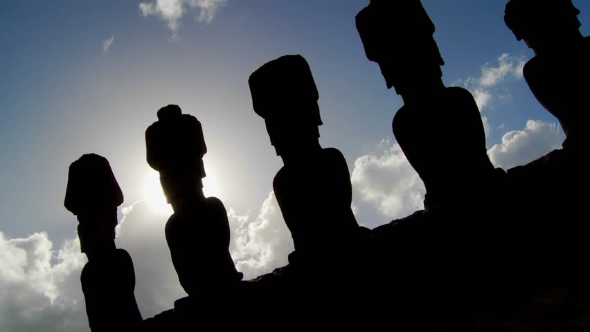 Easter Island statues are silhouetted against the sky.