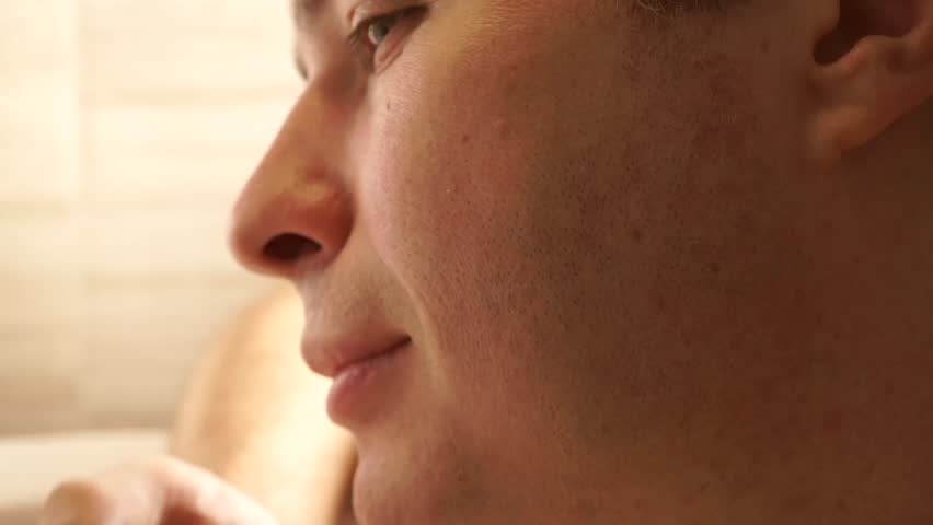 Young handsome man using his after shave balm, profile close up video