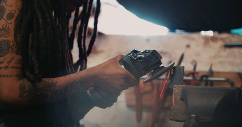 Afro craftswoman grinding metal in a functioning well-used workshop with sparks flying off the metal