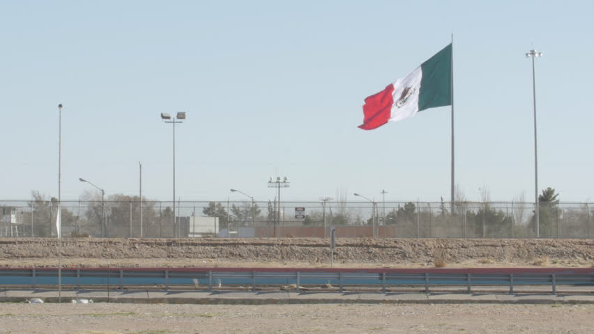 4K shot of the Mexican flag blowing slowly in the wind near the highway on the border of the US and Mexico in the daytime.
