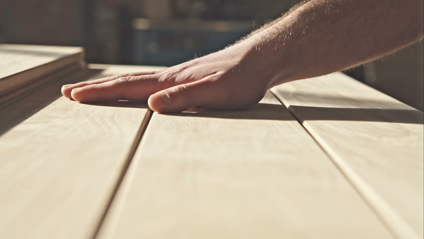 The young master hand touches the wooden boards in the sun. RAW video record.