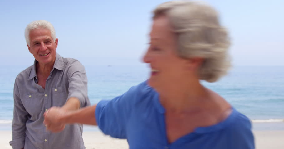 Old couple hugging and dancing at the beach