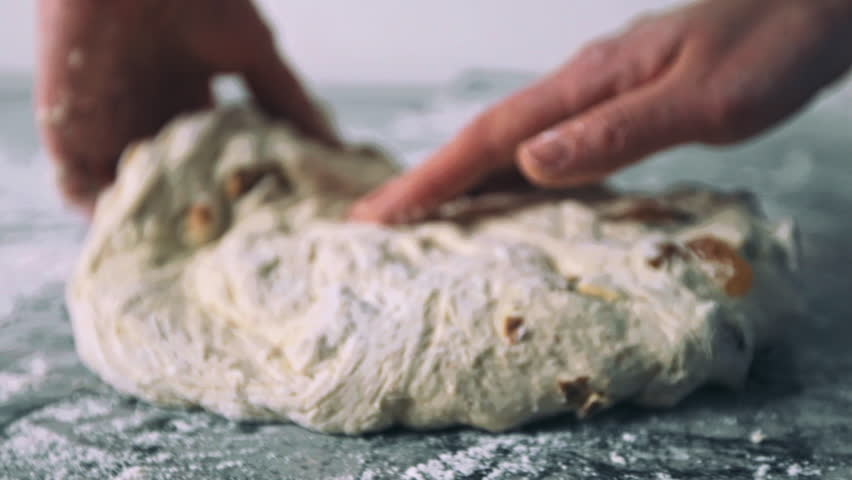 Female baker working with the organic sourdough bread with nuts and raisins