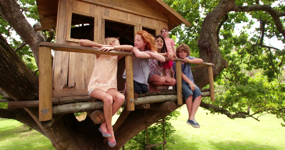 Low angle shot of a row of diverse children sitting on the edge of a wooden treehouse with their legs dangling in the air, smiling at the camera and surrounded by lush green leaves #14792257