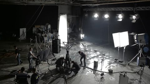KIEV/UKRAINE - FEB 15 2016: Preparations for the shooting film in a large hall, lot of equipment, lighting equipment, people are willing to work, black background, lighting fixtures throughout, gray