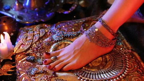 Indian Wedding Preparation. Luxury Oriental Fashion Accessories: Female foot and Hands, Beautiful National Indian Bridal Golden Jewellery. Eastern Traditional Sari clothes. Color lenses, Candlelight.