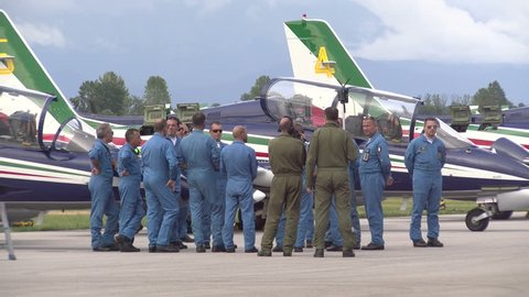 RIVOLTO, ITALY, SEPTEMBER 6: Mechanics chat beside the Aermacchi MB-339-A, planes of the aerobatic demonstration team of the Italian Air Force, before 55th anniversary event, on September 6, 2015