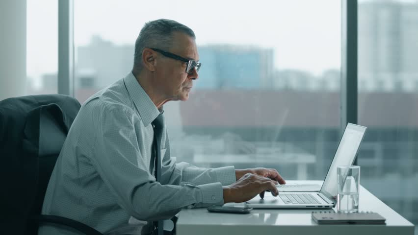 modern office look. exellent office elderly businessman look at phone and working with computer in modern office   4k stock video on modern office look