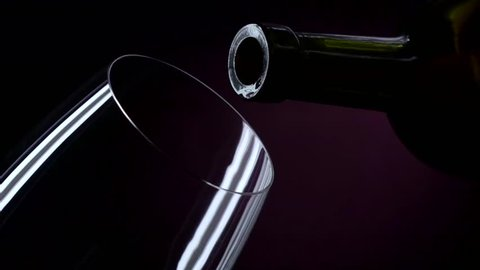 The bottle of wine, the wine is poured into a glass, black, closeup, slowmotion