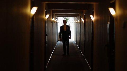 Young man go along te corridor with bouquet