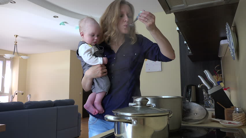 Nanny with infant baby in hands cooking mix meal dish in pot and taste it with spoon. Housewife multitasking at home. Vapor steam rise. Static shot. video clip. | Shutterstock HD Video #14835433