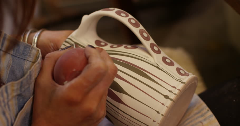 Close-up shot of a young woman at workbench painting ceramics in pottery studio.