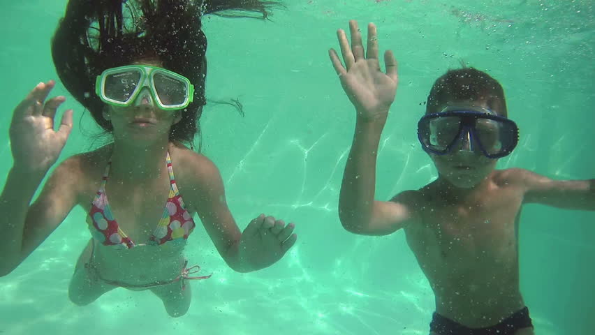 Kids Swimming Underwater three kids swimming in pool underwater stock footage video