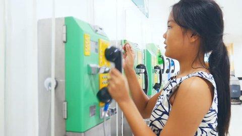 Asian teen using public telephone at school