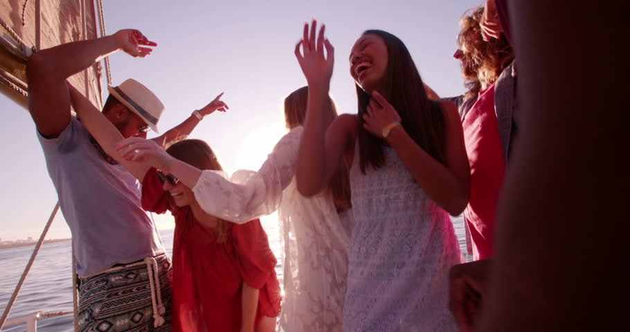 Group of friends of mixed races dancing and drinking together at a party on a yach at sunset with soft evening sunflare in Slow Motion
