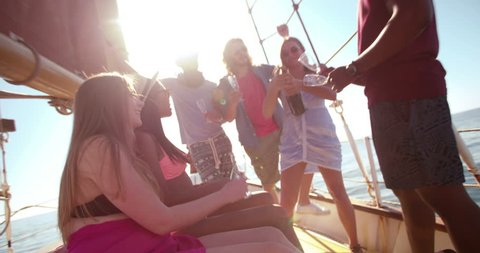 Mixed race friends having a party and drinking champagne on a yacht with summer sunflare