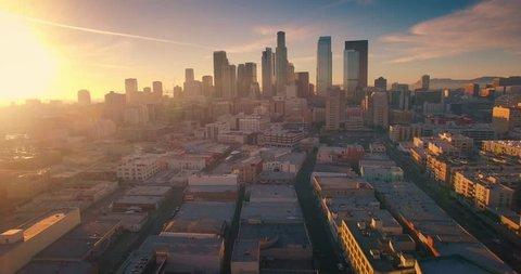 Aerial view of city of Los Angeles downtown skyline at sunset. Camera flying backward. 4K UHD.
