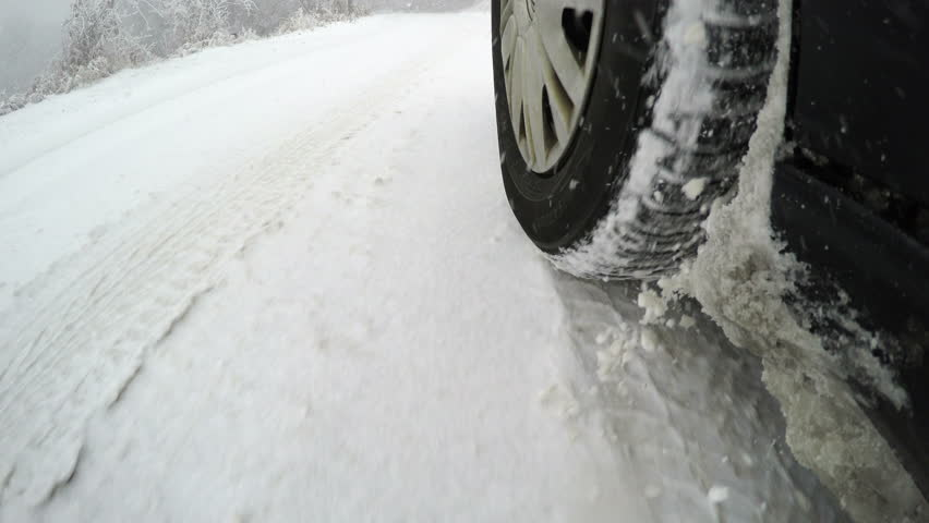 Car driving through a winter storm with snow on a forested road