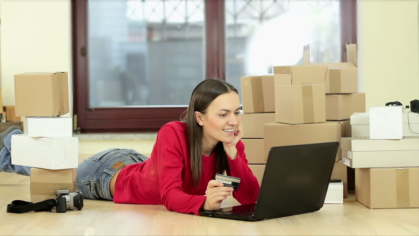 Cheerful young woman using her laptop and credit card for home shopping while lying on the floor beside stack of boxes | Shutterstock HD Video #14928097