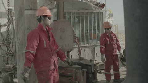 Kuwait Oil Industry. A group of Asian oil riggers are screwing a shaft tight on an oil rig in the desert.