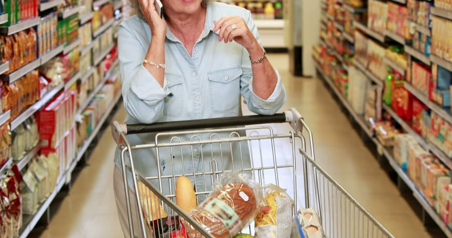 Senior woman talking on phone in the supermarket in high quality 4k format | Shutterstock HD Video #14948767