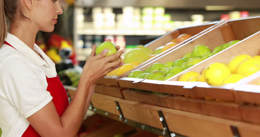 Pretty worker stocking the fruit in supermarket in high quality 4k format