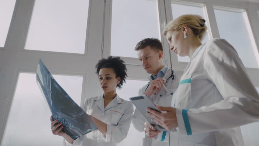 Healthcare, medical: Group of multi-ethnic doctors discussing and looking x-ray in a clinic or hospital. UHD 4K