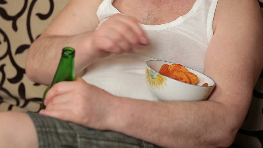 Lazy fat man watching Tv and drink beer with potato chips on couch