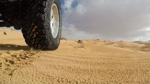SAHARA DESERT, TUNISIA - CIRCA OCTOBER 2015: action cam on a rod,  low lateral view:  off road cars on dunes in the desert.