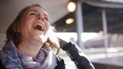 4K Young woman laughs and pokes her tongue at the camera