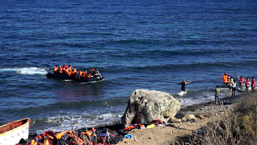 Refugees swim up to the coast by the boat. Lesbos, Greece. October 14, 2015. A dangerous and illegal way through the sea from Turkey to the Europe. People help them to get out of the boat ashore.