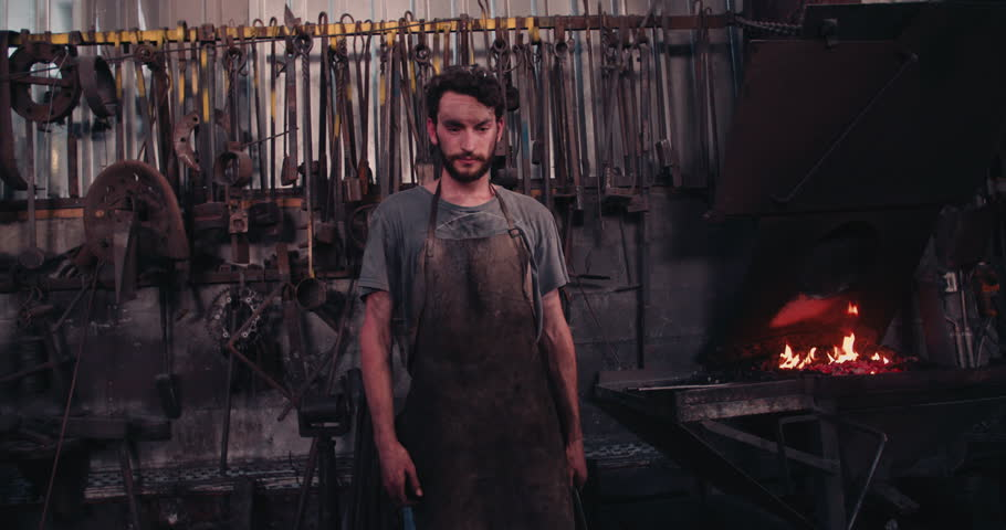 Blacksmith portrait. Young adult bearded man standing in his workshop showing fullfilment with folded arms.