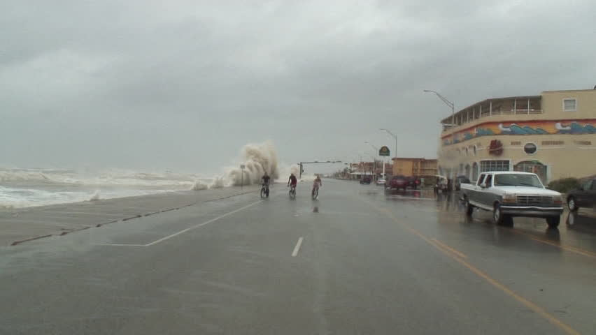 Hurricane Storm Surge hits a seawall and knocks down two cyclists hard | Shutterstock HD Video #15050956