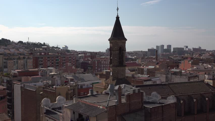 Peaked bell tower of Catholic church rise above city roofs, cityscape panorama. Static camera shows Sant Angel Custodi basilica belfry, Hostafrancs area at Sants-Montjuic district of Barcelona city