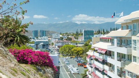 NOUMEA, NEW CALEDONIA - 2016: Vibrant Island City Scene with Colorful Flowers Buildings and Vehicles with Majestic Mountains in the Background