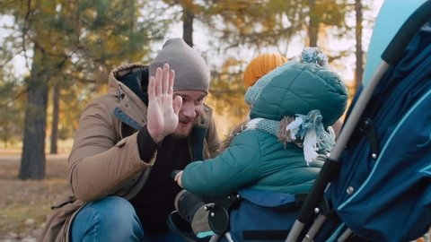 Mom and dad playing with their baby sitting in stroller: father giving son high five and smiling
