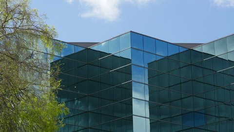 OFFICE BUILDING ESTABLISHING SHOT.  GEOMETRIC BLUE GLASS OFFICE BUILDING REFLECTING THE SKY ABOVE.  TREES BLOWING IN THE BREEZY FOREGROUND WITH A BLUE & CLOUDY SKY BACKGROUND.  IN 4K.