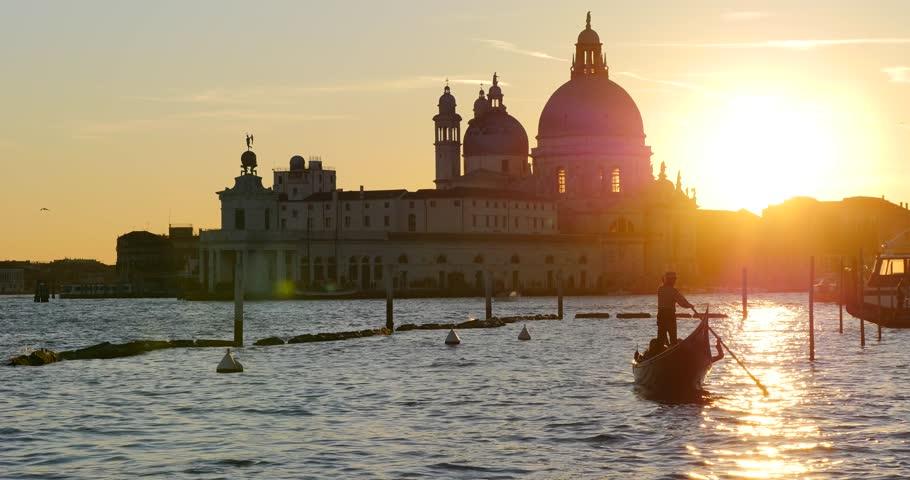 Gondola with Santa Maria Della Salute at sunset, Grand canal. Venice, Italy.