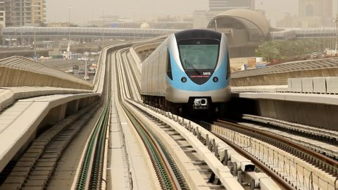 Dubai metro train move away along elevated railway, telephoto view back, fine perspective, rear cabin of carriage, ride far. Slight slope at rails, lowering and turn a little, next station seen afar