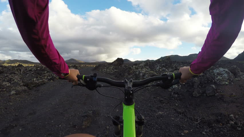Female cyclist riding bicycle on rocky landscape. Dedicated young woman in sportswear is cycling in nature living her healthy lifestyle. Lanzarote, Canary Islands, Spain. Shaky ACTION CAMERA POV.