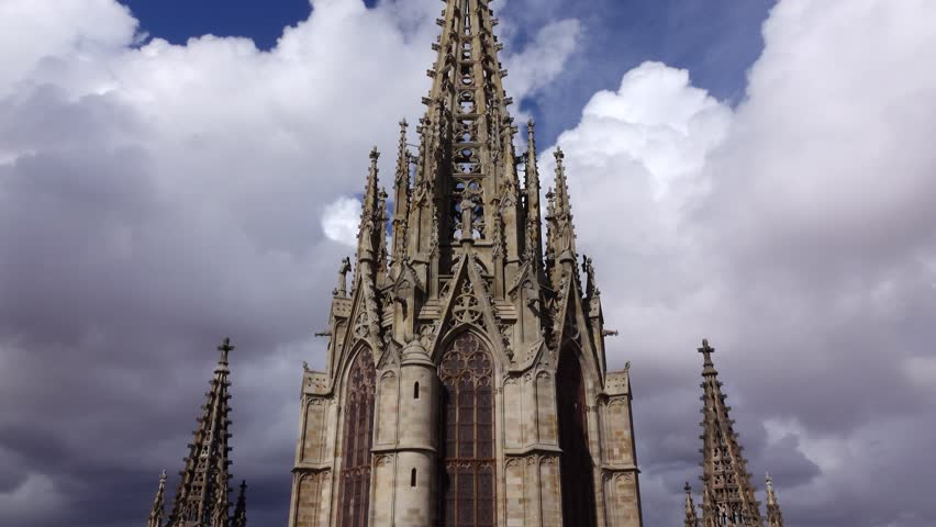 Dolly camera move at top of Gothic church, low angle openwork spire against cloudy sky. Barcelona Cathedral details, rooftop observation deck, low angle shot of main facade spire from back side