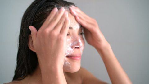 Ethnic woman washing face with facewash in shower. Closeup of Asian female young adult holding bottle foaming cleasing soap or scrub on skin in warm water shower bath.